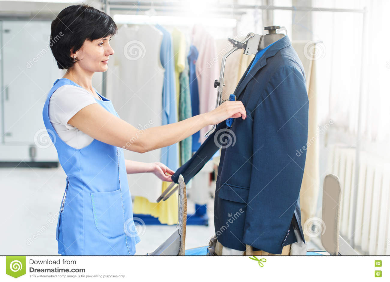 Trabalhador fêmea no serviço de lavanderia o processo de trabalho no equipamento automático universal para cozinhar, passar e lim
