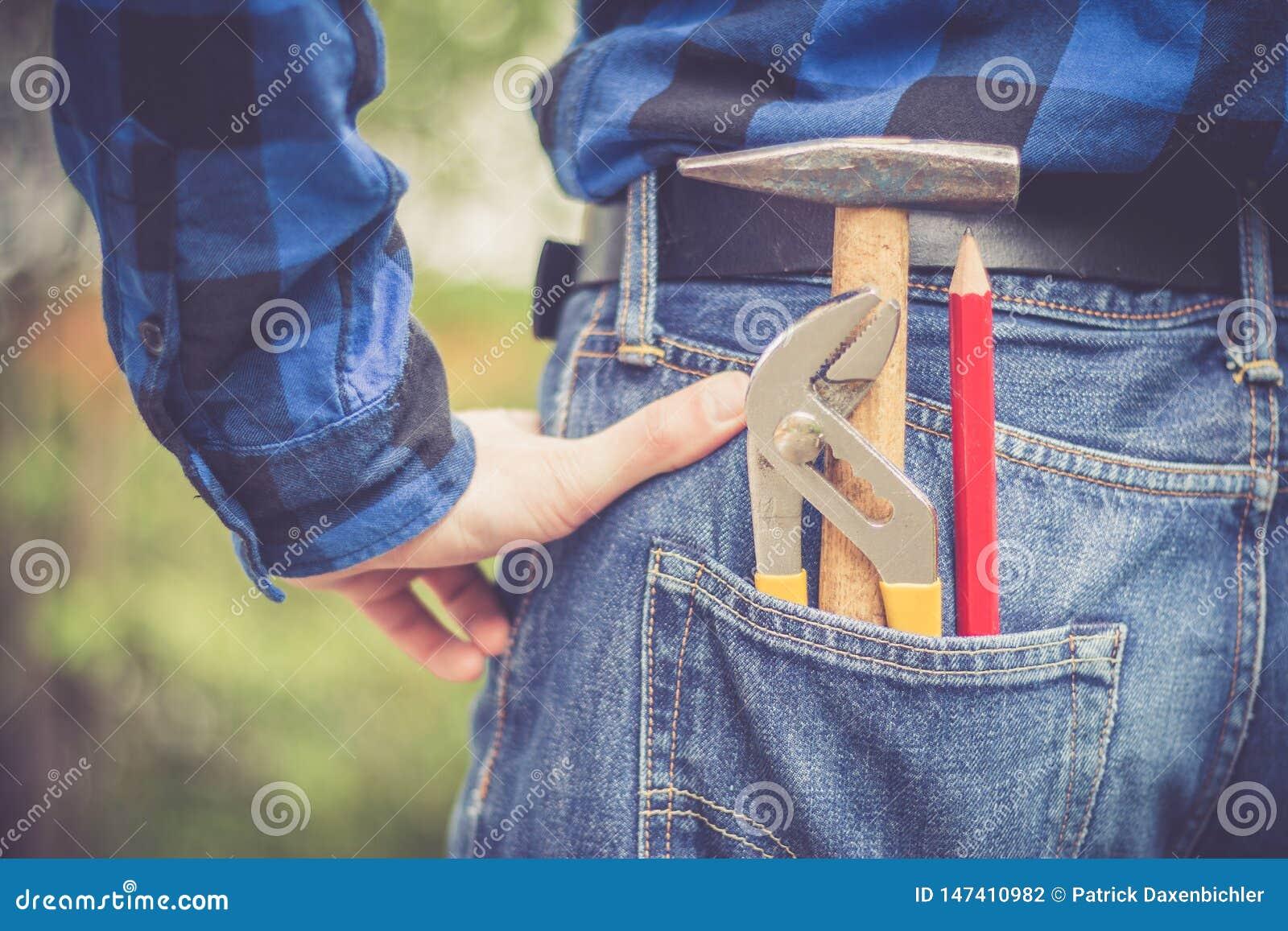 Trabalhador manual da casa: Opini?o traseira um homem novo com martelo, l?pis e prendedor em seu bolso