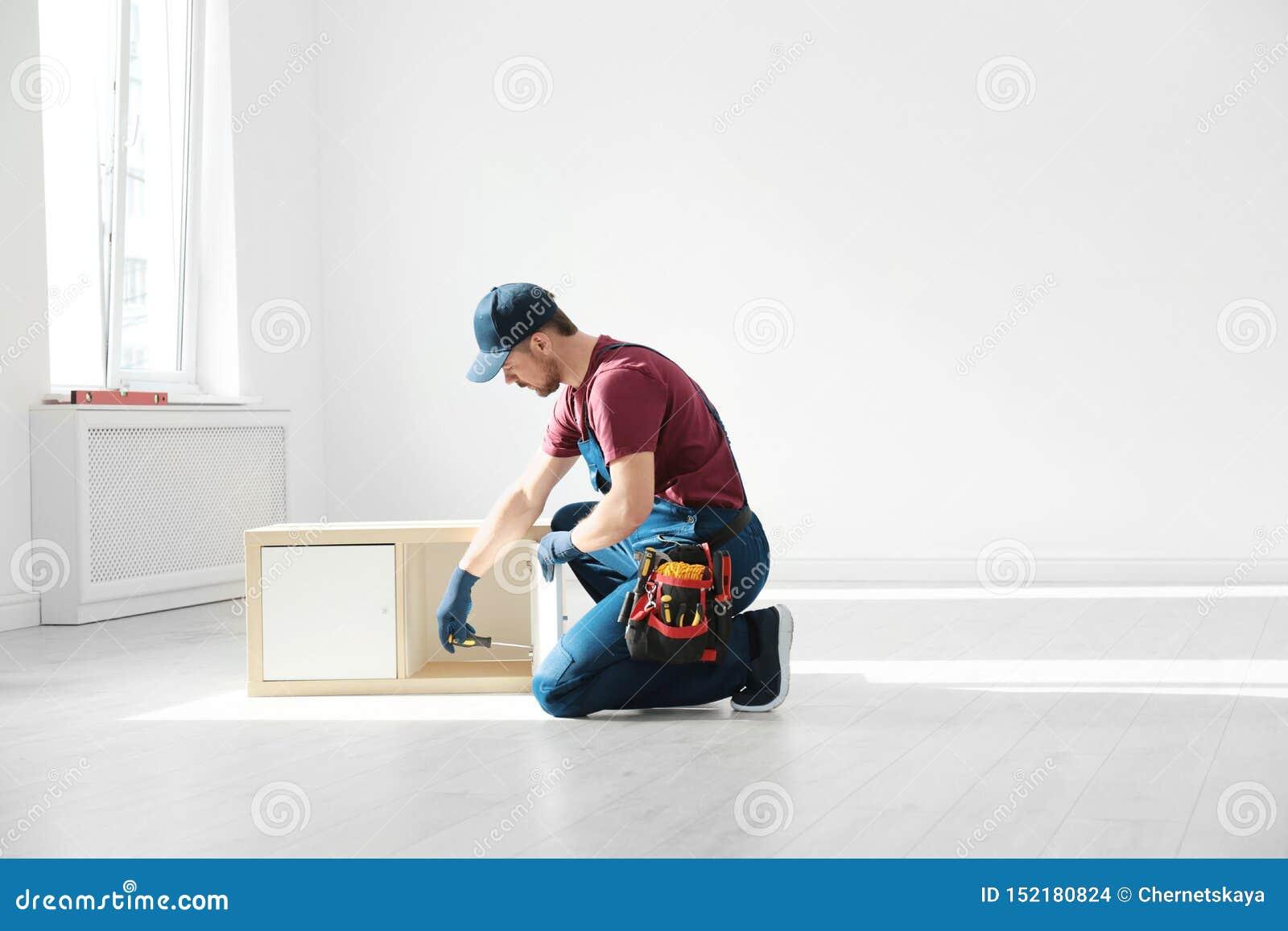 Trabalhador manual na mobília de montagem uniforme dentro Ferramentas profissionais da constru??o