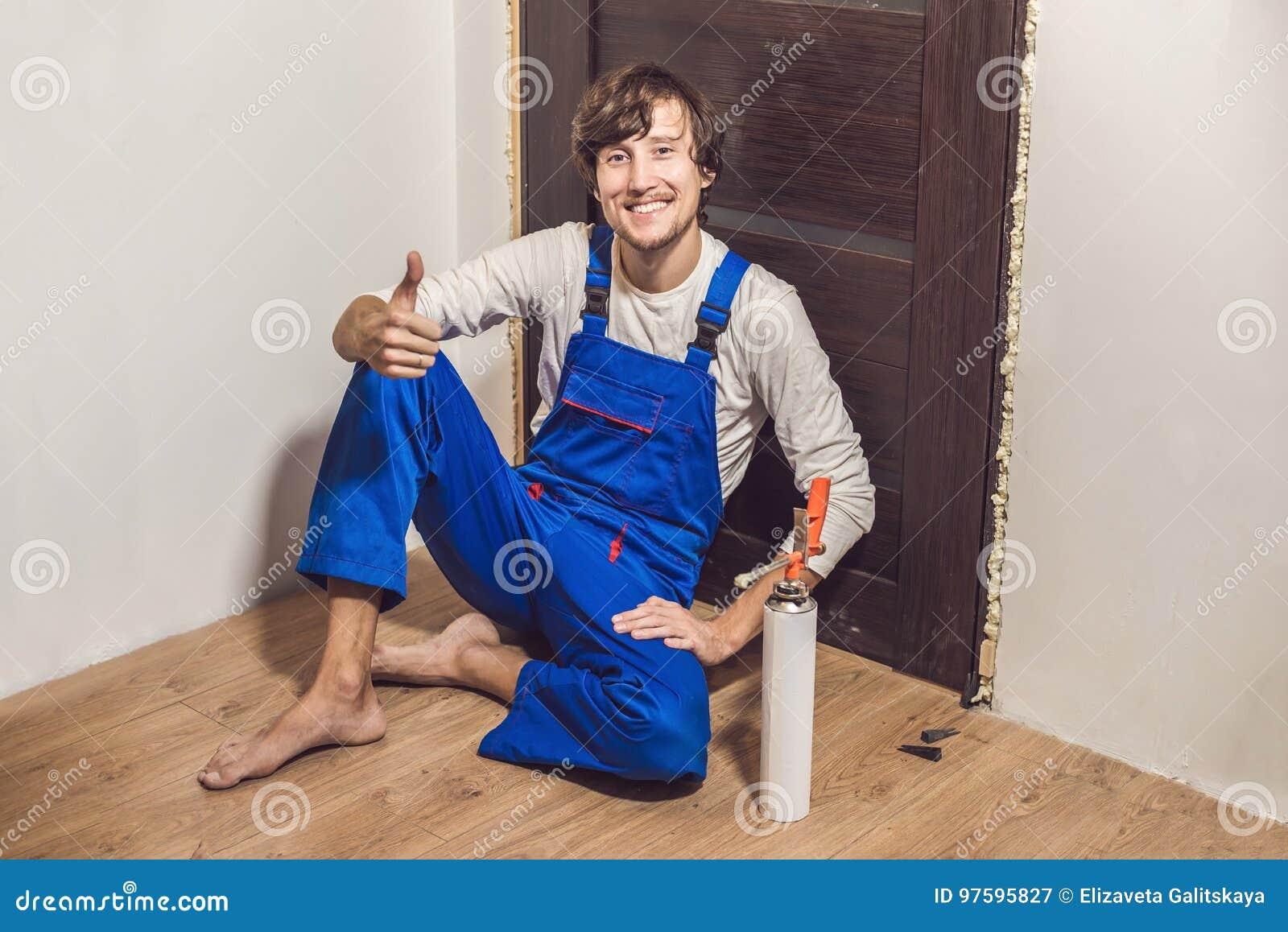 Trabalhador manual novo que instala a porta com uma espuma da montagem em uma sala