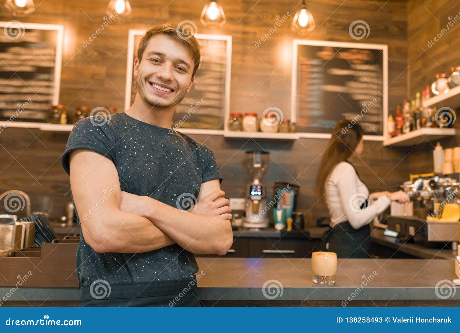 Trabalhador masculino novo da cafetaria do barista que sorri olhando a câmera com os braços dobrados cruzados perto do contador d