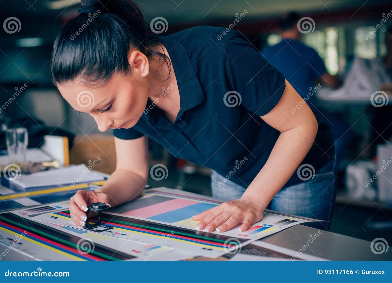 Trabalhador na impressão e em usos centar da imprensa uma lupa