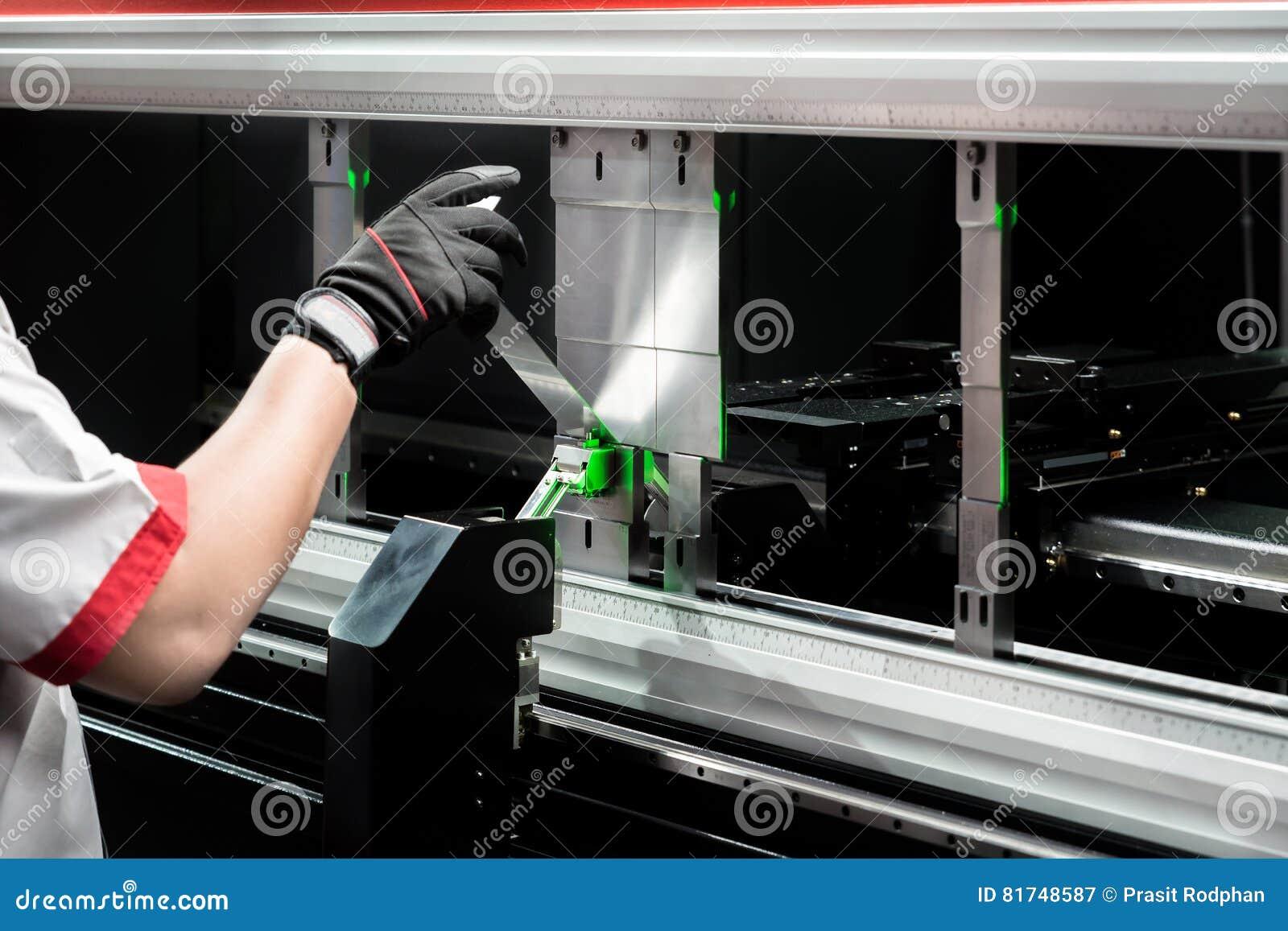 Trabalhador na oficina da fabricação que opera a máquina de dobramento cidan