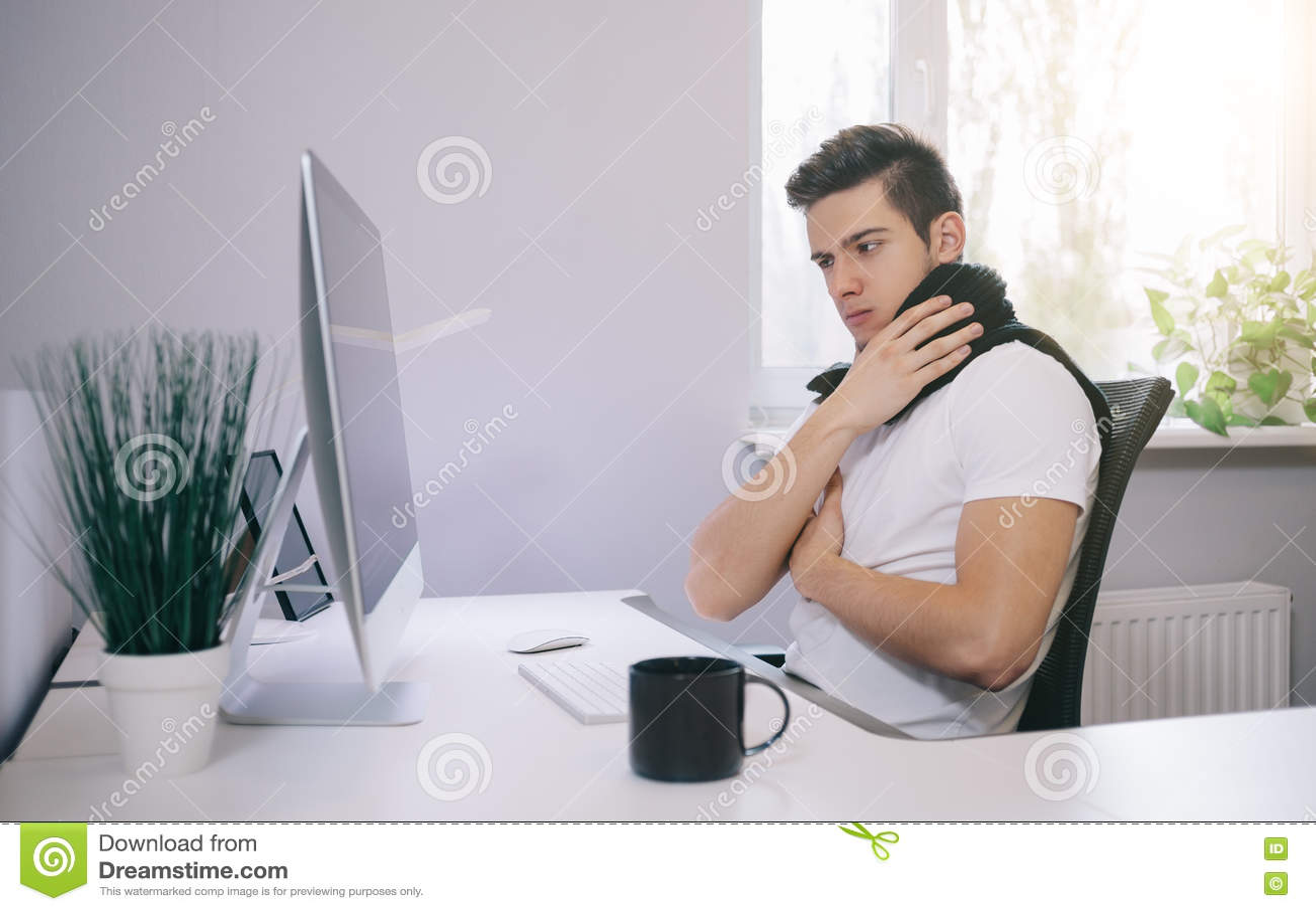 Trabalhador novo com um frio Freelancer no lenço e no copo do chá no escritório Desenhista a garganta doente no