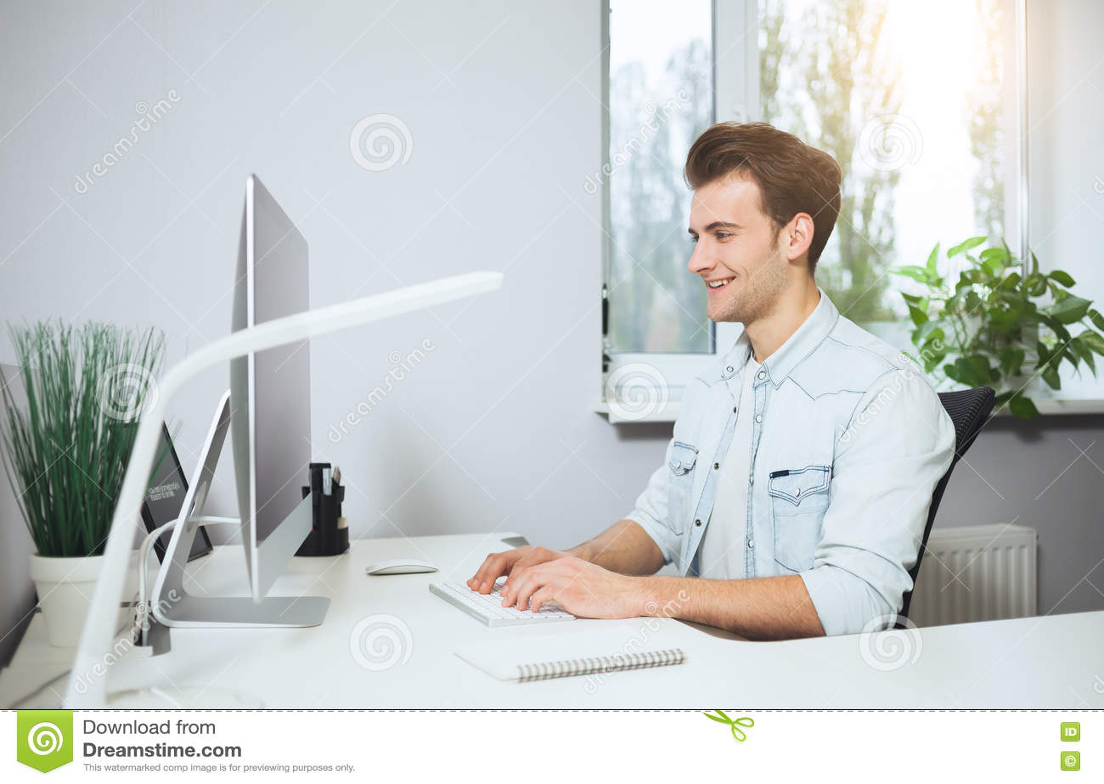 Trabalhador novo que senta-se em um escritório no computador Freelancer em uma camisa branca O desenhista senta-se na frente da j