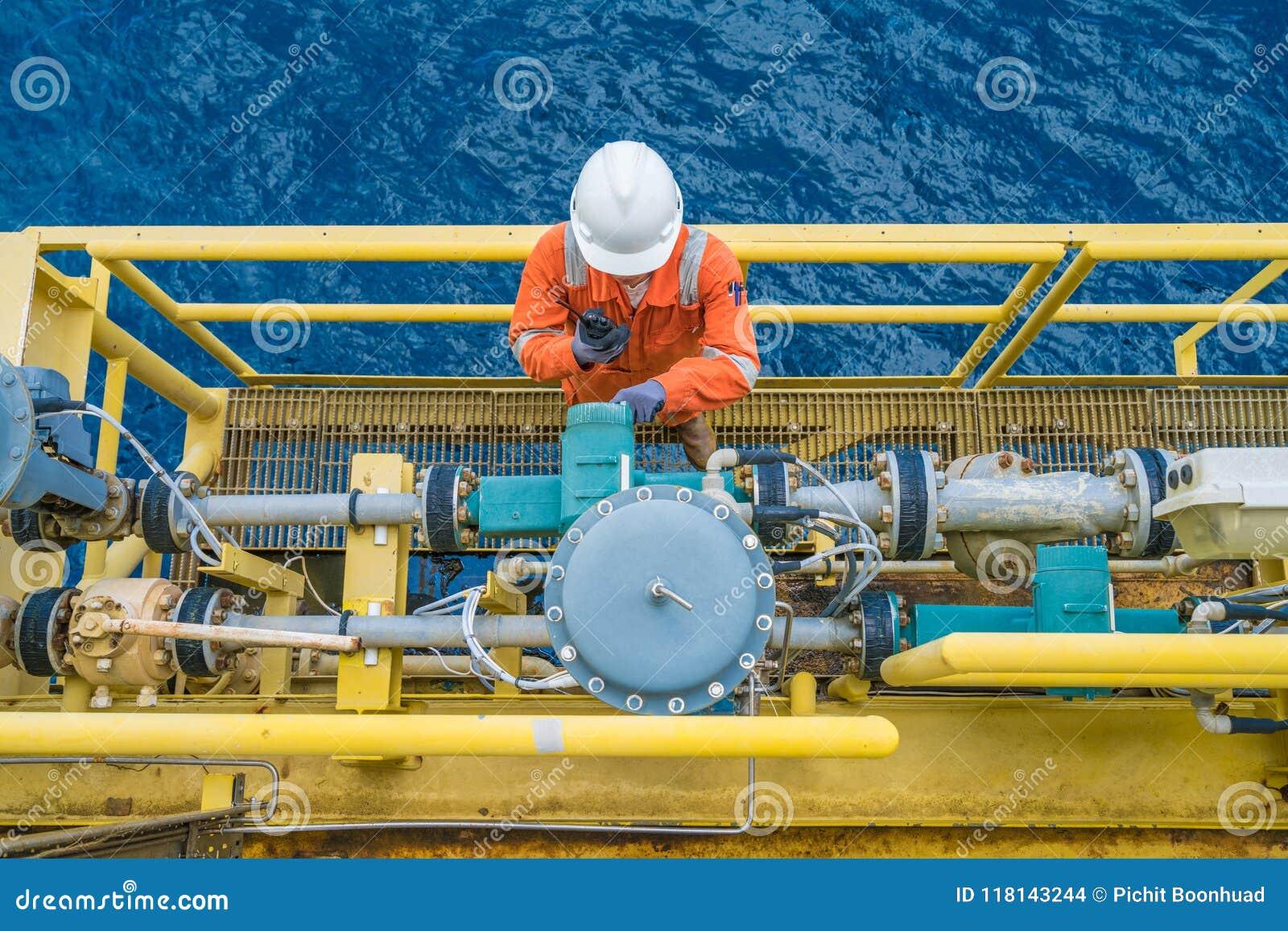 Trabalhador a pouca distância do mar da plataforma petrolífera que verifica o parâmetro do medidor digital do transmissor de flux