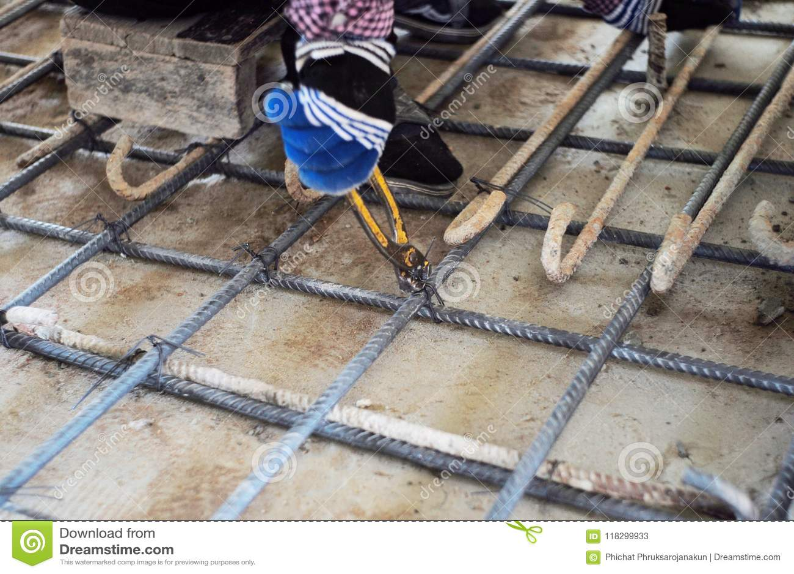 Trabalhador que faz o objeto metálico para o reforço do assoalho concreto no canteiro de obras