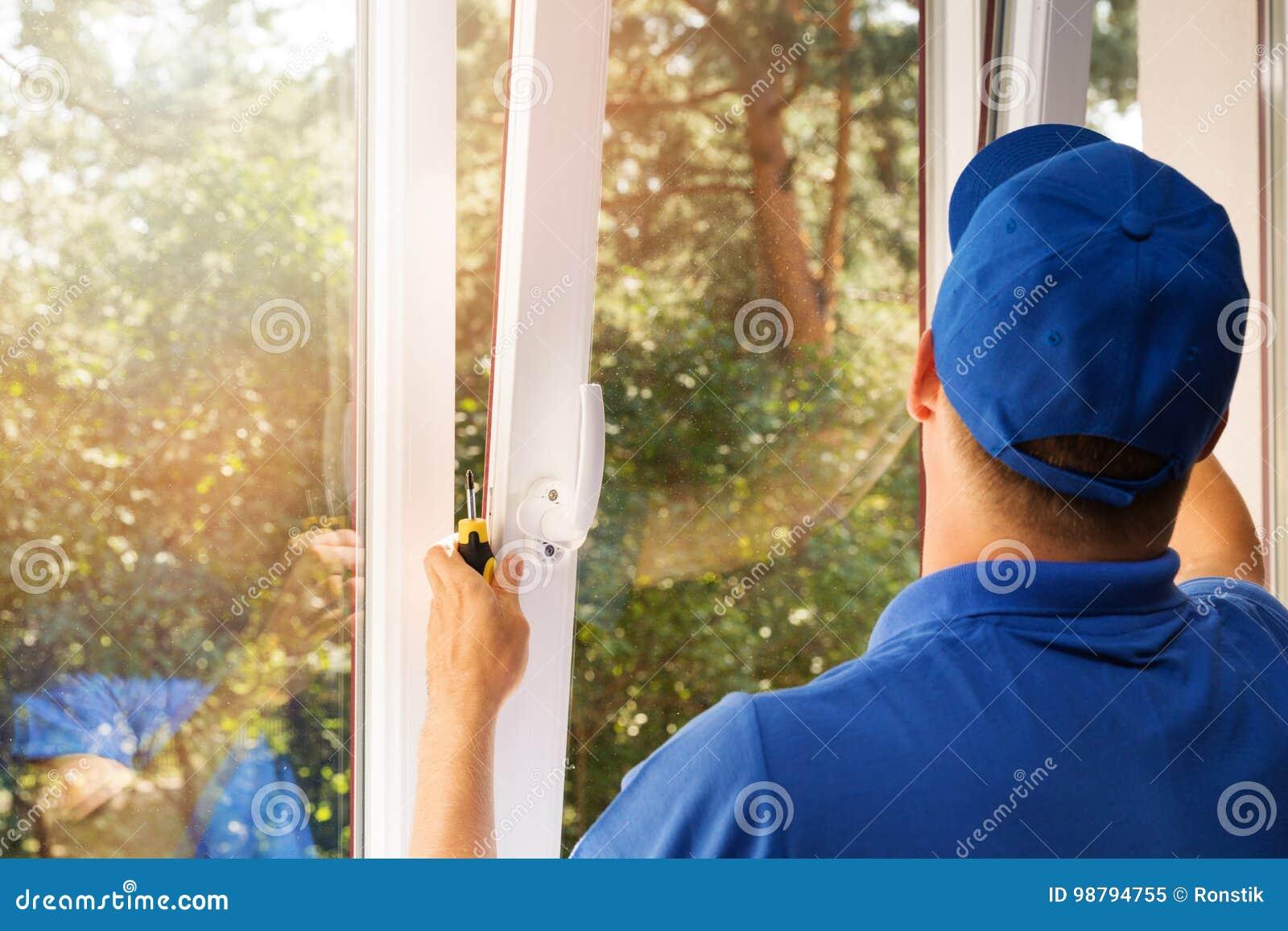 Trabalhador que instala a janela nova do pvc do plástico