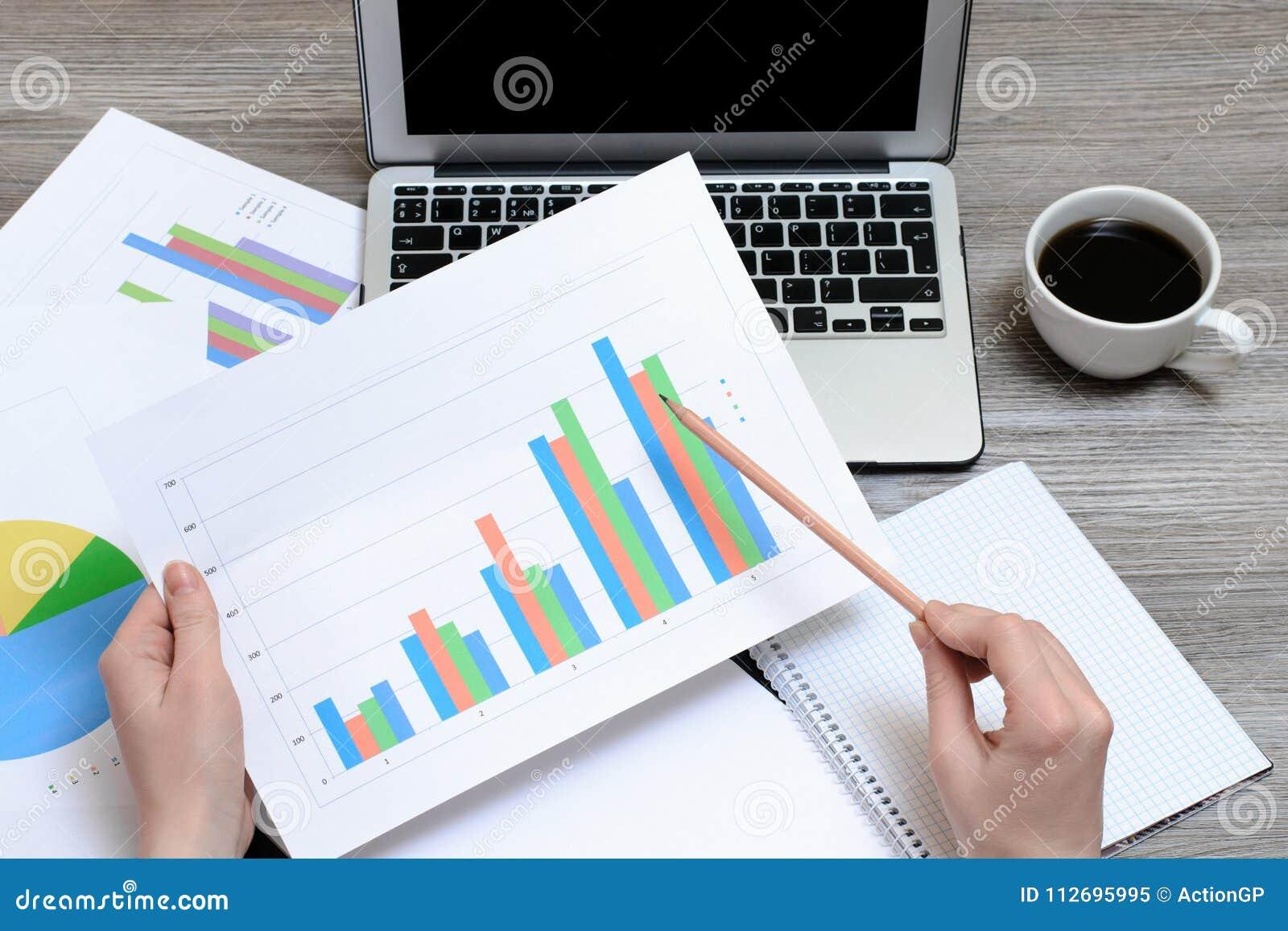 Trabalhador que olha gráficos Vista superior nas mãos que guardam gráficos, portátil, xícara de café, estação de trabalho do loca