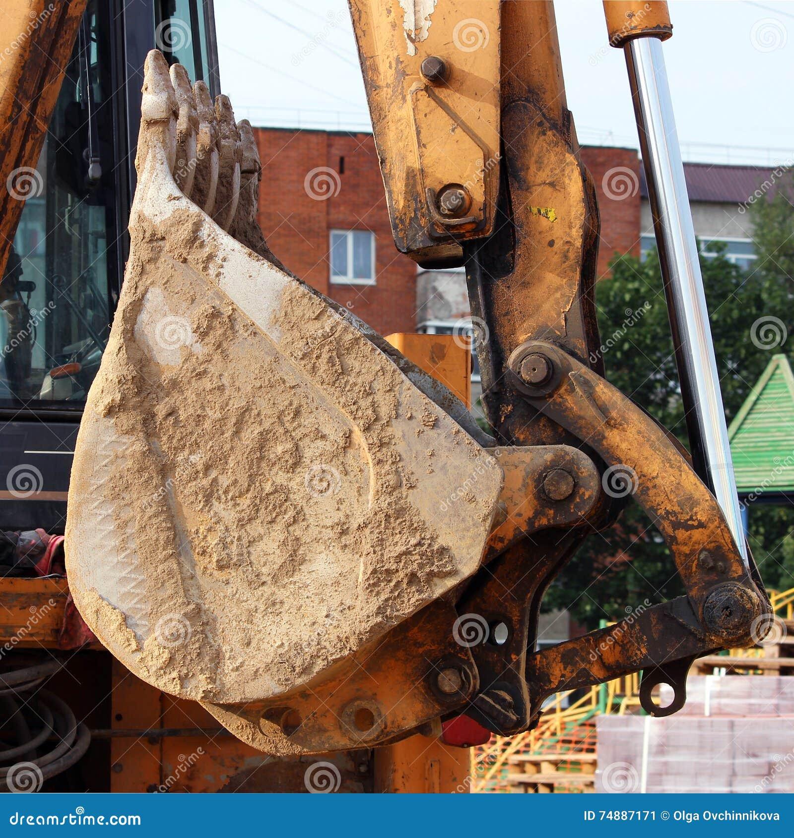 Trabalhador sujo do carregador de cubeta que trabalha na praça da cidade movendo páletes de pavimentos
