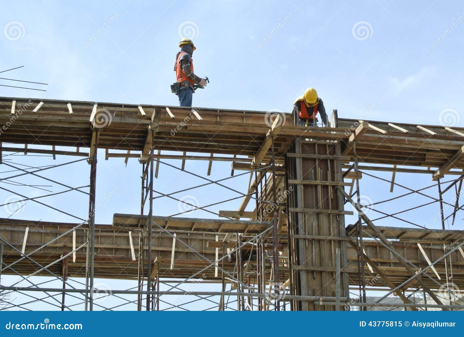 Trabalhadores da construção que instalam o molde do feixe