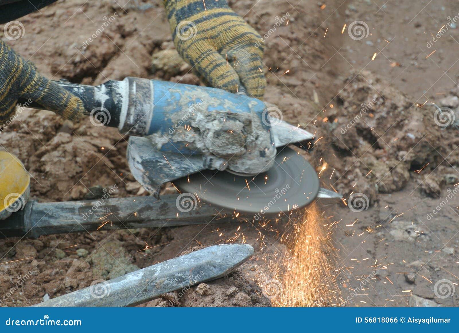 Trabalhadores da construção que usam o moedor da construção para apontar o aço no canteiro de obras