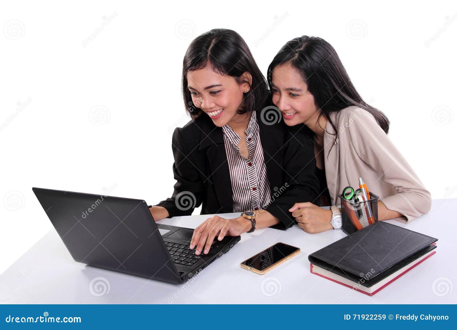 Trabalhadores de escritório fêmeas que usam o portátil junto