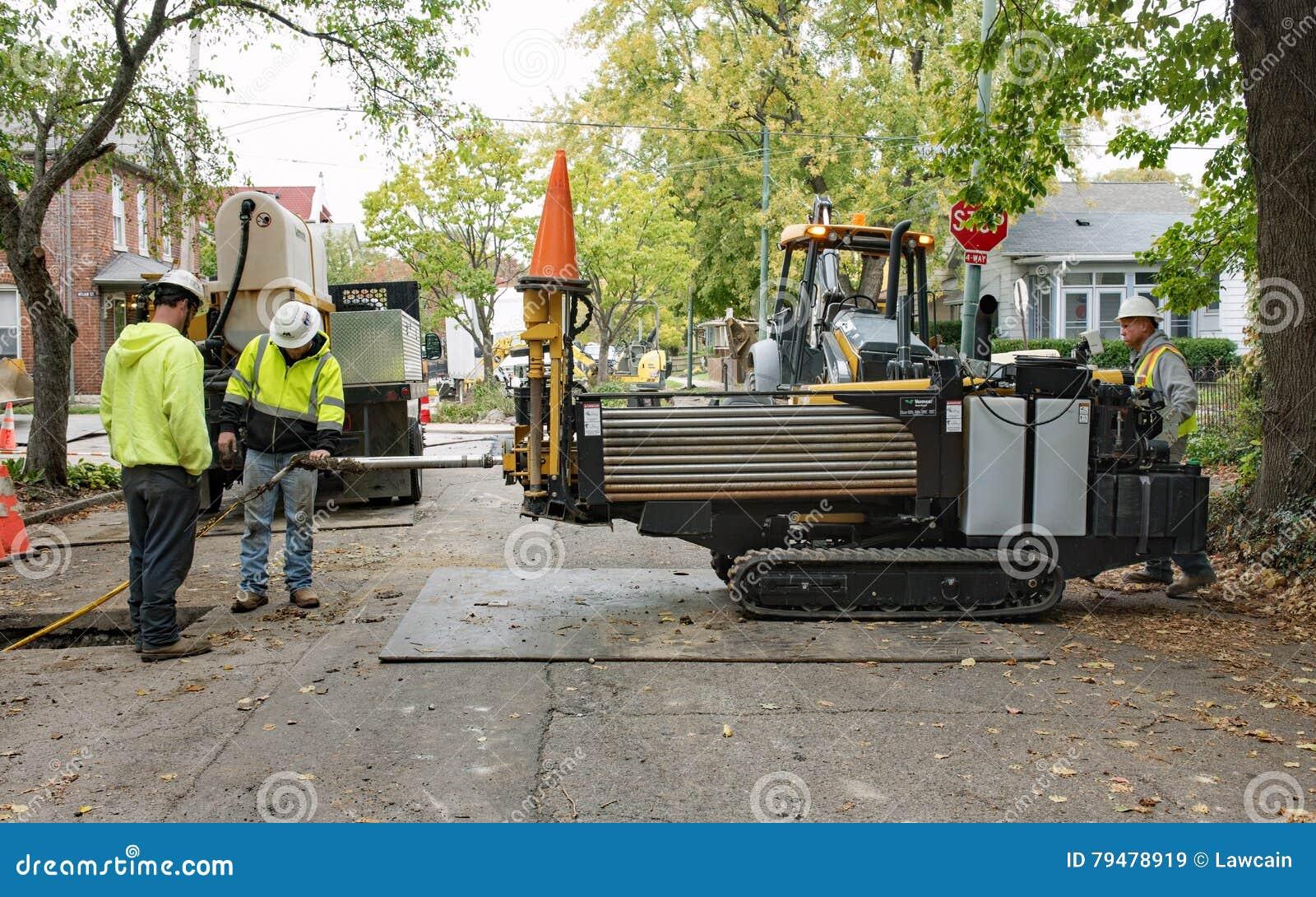 Trabalhadores do encanamento que usam a broca direcional horizontal