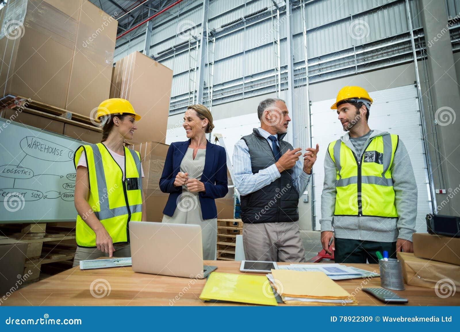 Trabalhadores e gerentes do armazém que interagem um com o otro