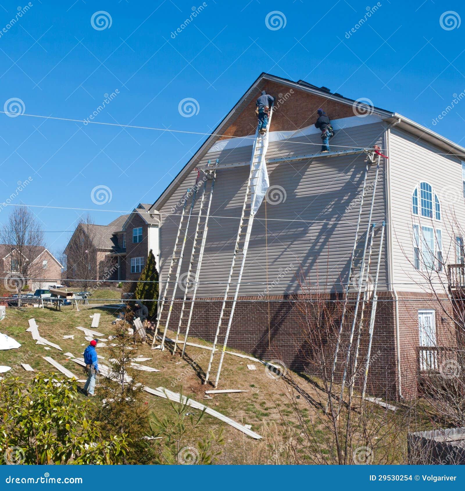 Trabalhadores que instalam os painéis de tapume plásticos na casa de duas histórias.