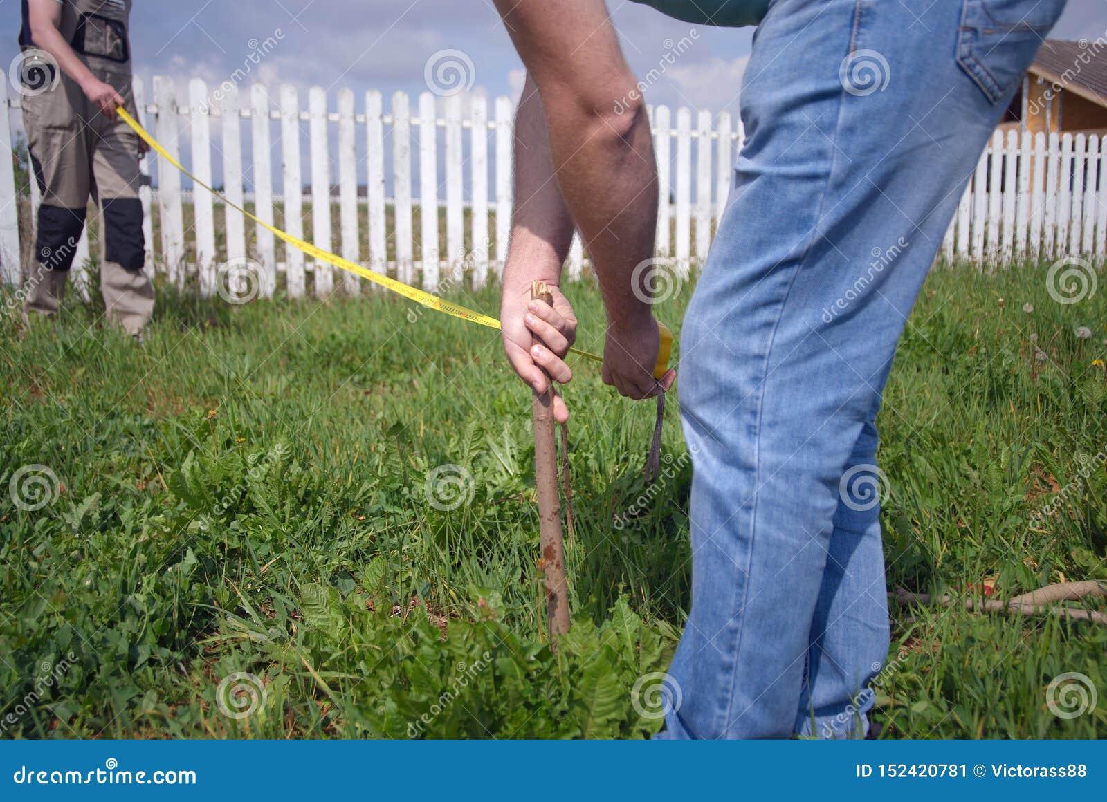 Trabalhadores que medem a terra com uma régua