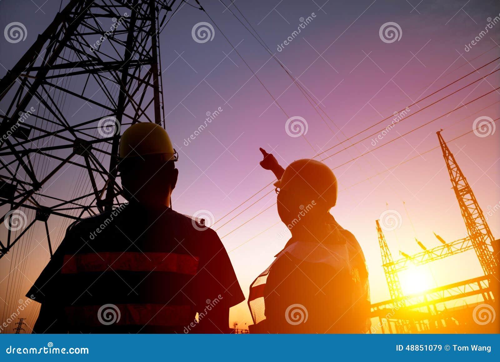 Trabalhadores que olham a torre e a subestação de poder com por do sol b