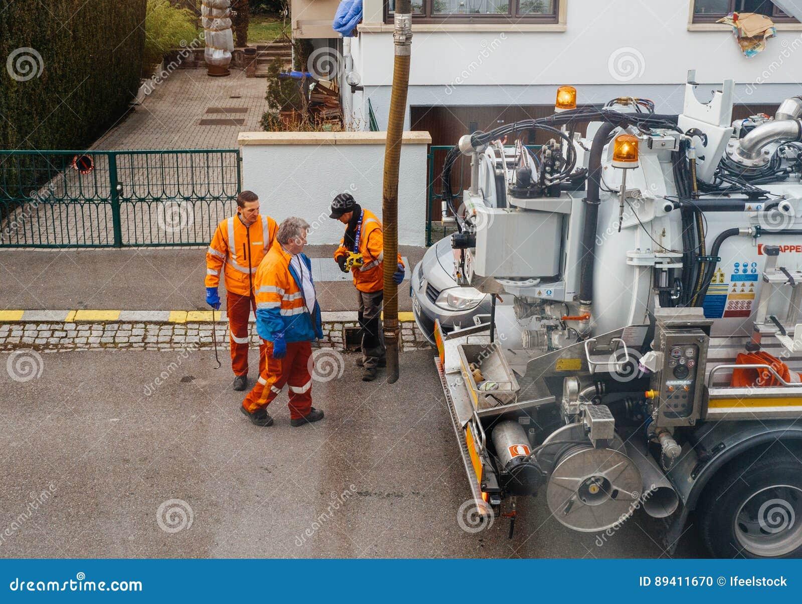 Trabalhadores que usam o caminhão do esgoto e a grande tubulação que trabalham no clogg