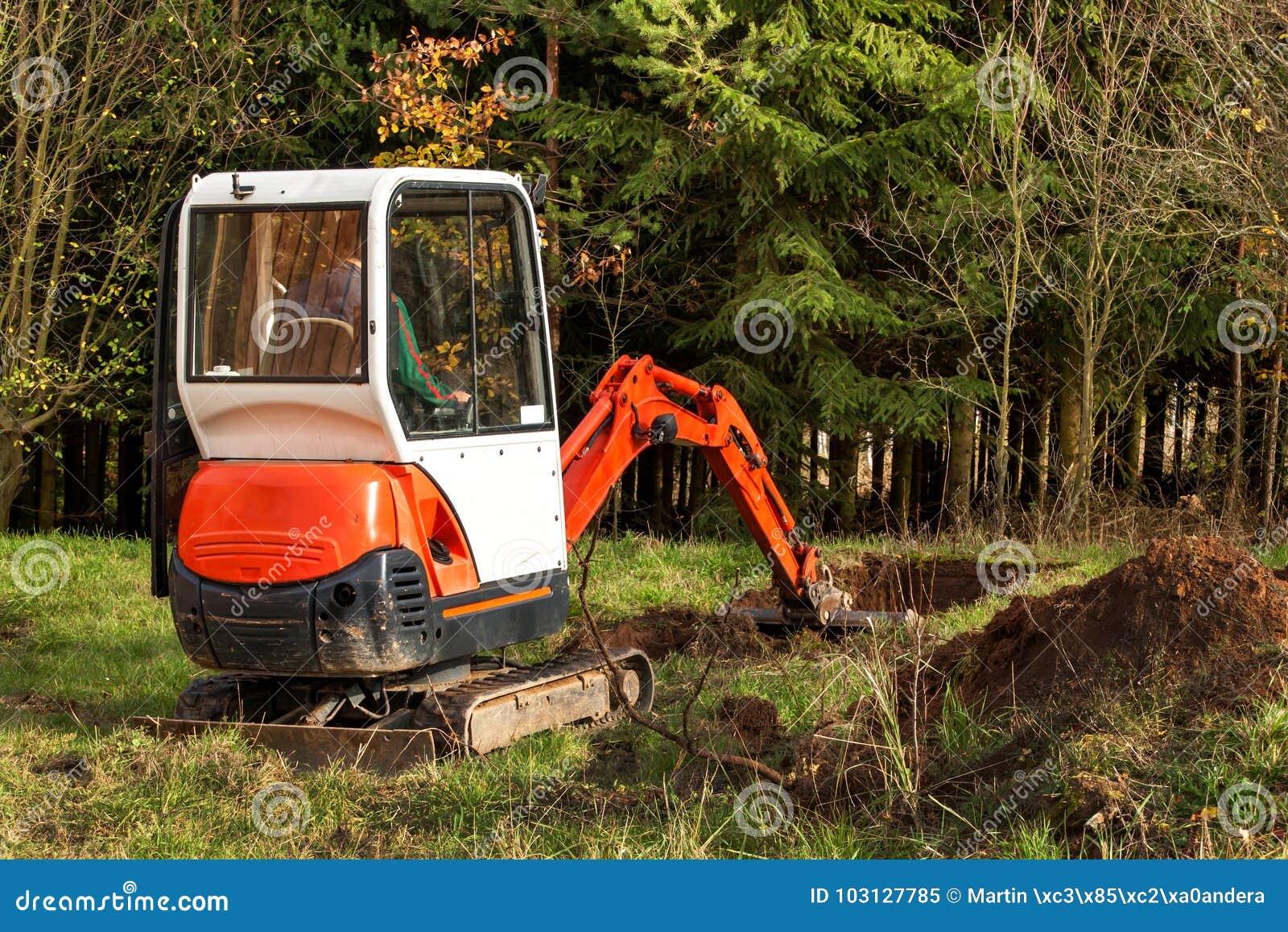 Trabalhe no canteiro de obras de uma casa ecológica A máquina escavadora ajusta o terreno Um escavador pequeno no jardim