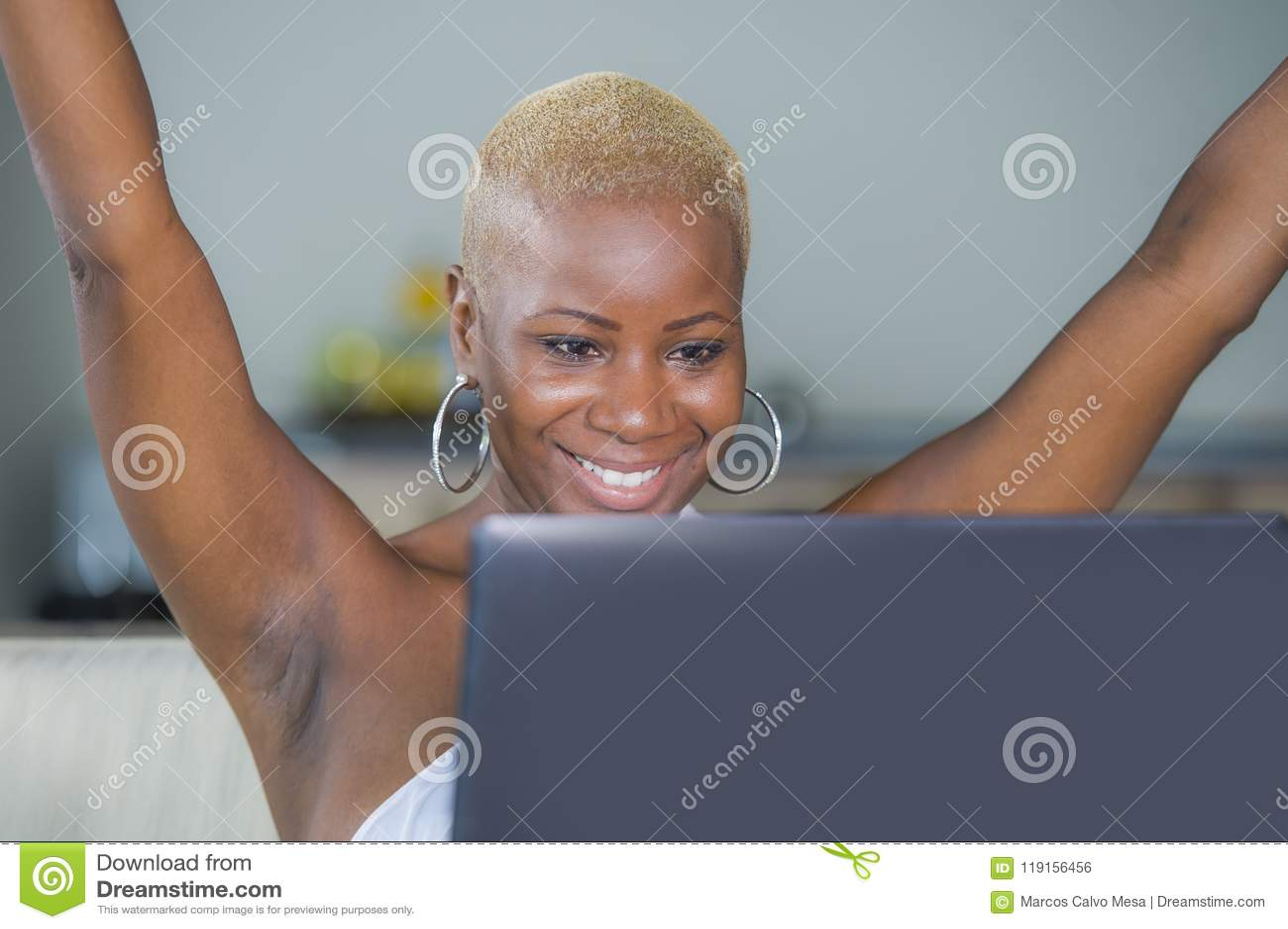 Trabalho de sorriso da mulher afro-americana preta feliz bonita nova no laptop em casa relaxado no sofá do sofá que comemora o su