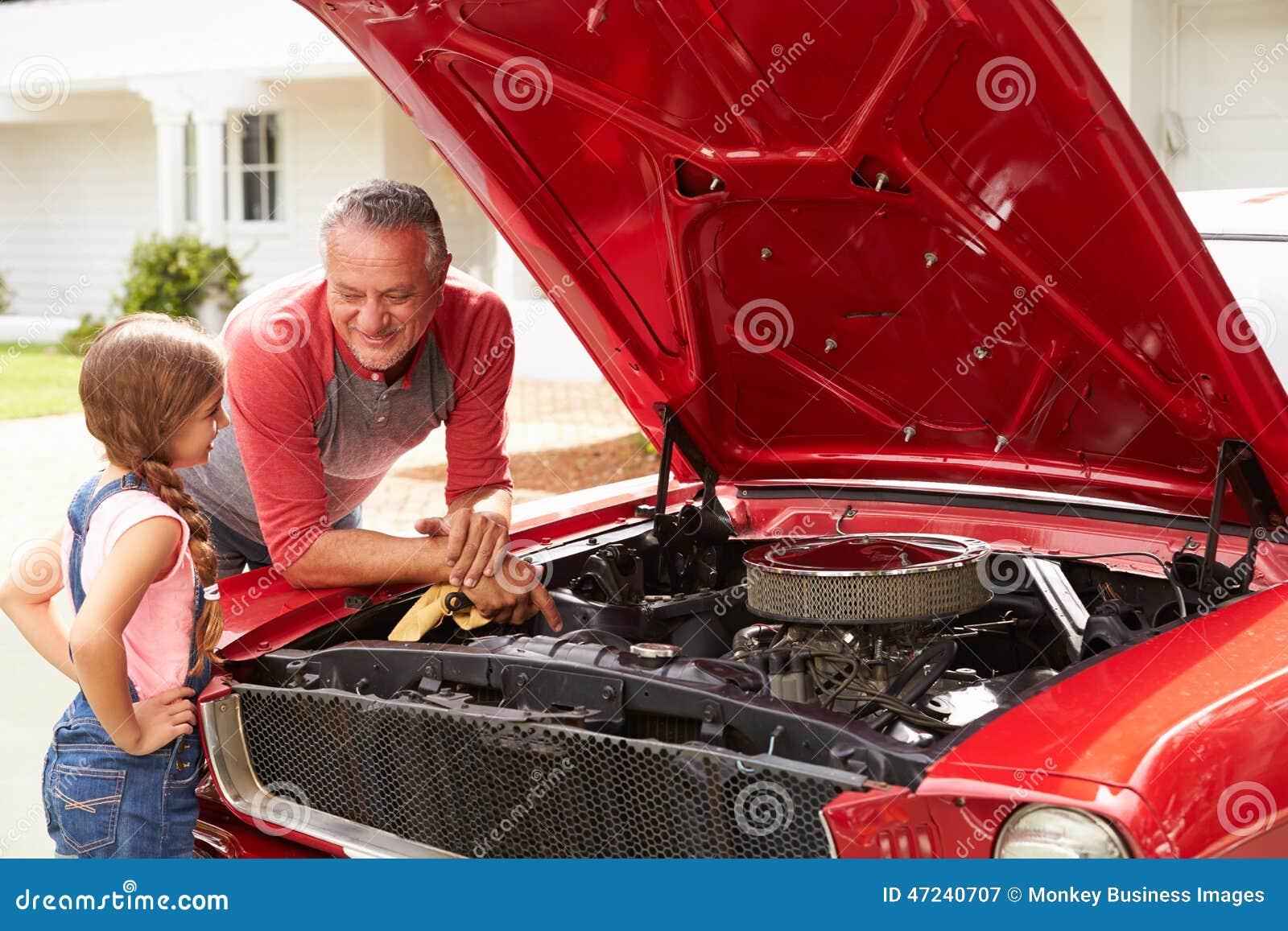 Trabalho do avô e da neta no carro clássico restaurado