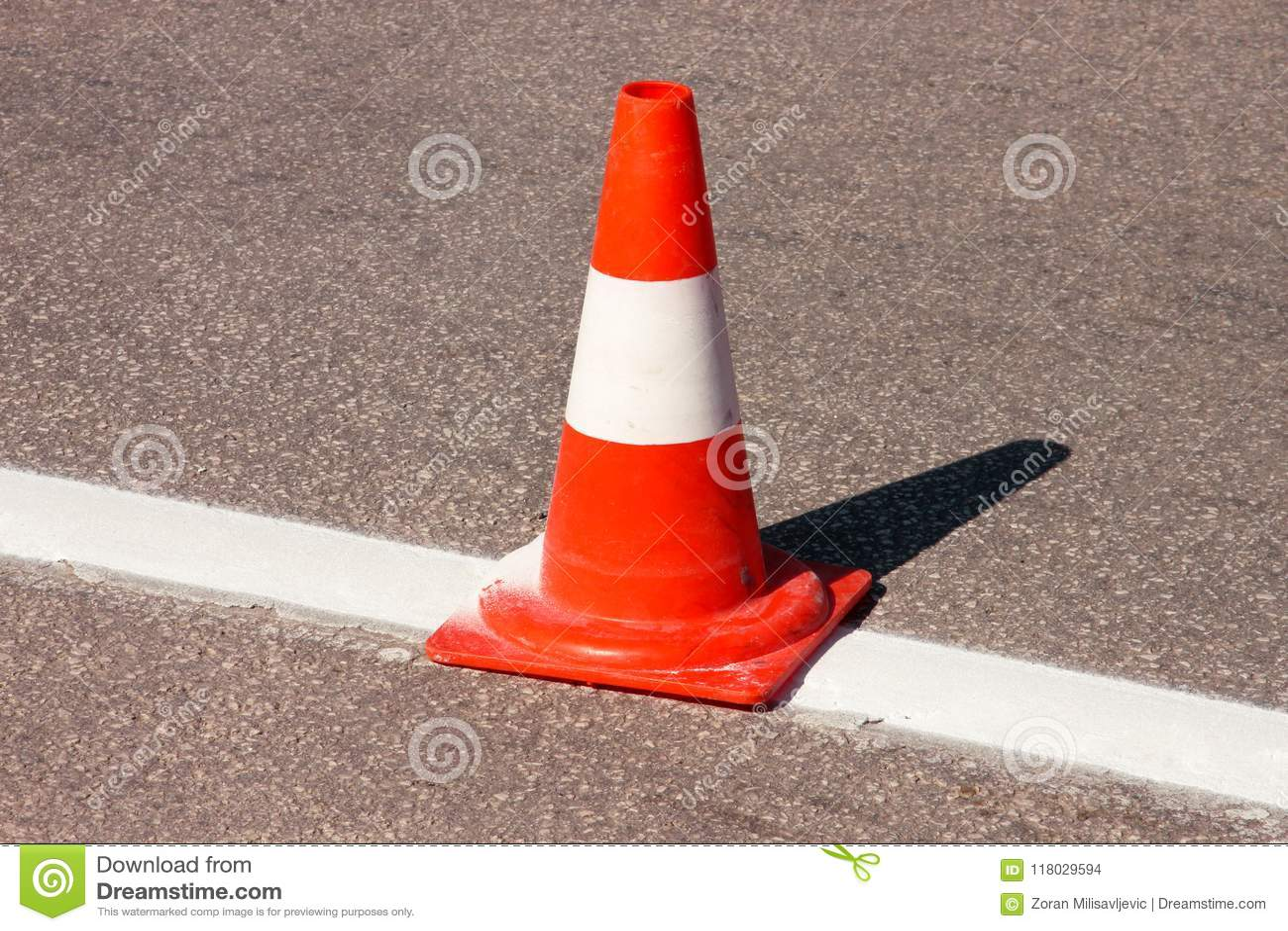 Trabalho na estrada Cone da construção Trafique o cone, com as listras brancas e alaranjadas no asfalto Sinais da rua e de tráfeg