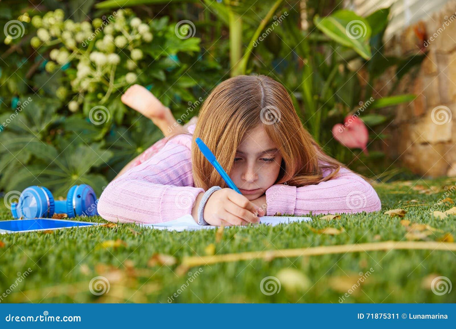 Trabalhos de casa louros da menina da criança que encontram-se no relvado da grama