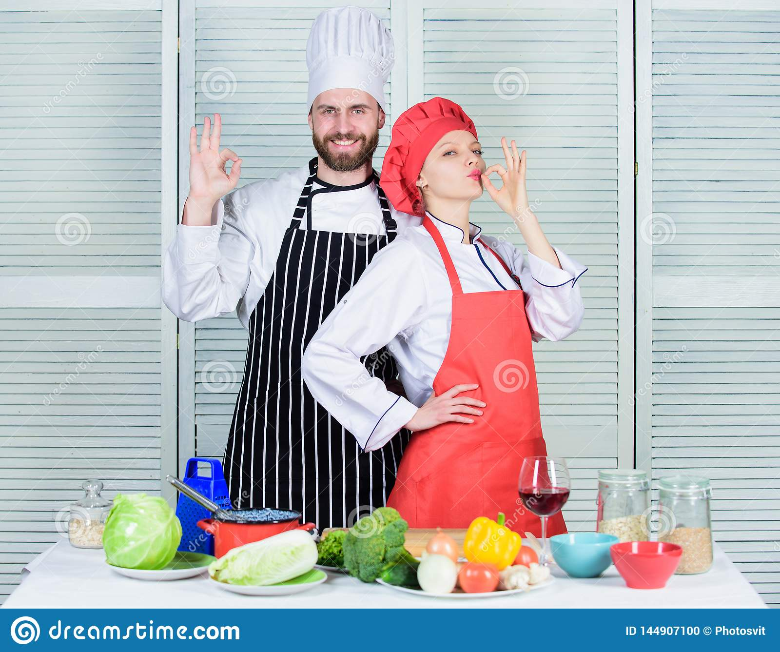 Trabalhos de equipa na cozinha Acople o cozimento do comensal S?cios culin?rios da mulher e do homem farpado Jantar delicioso da