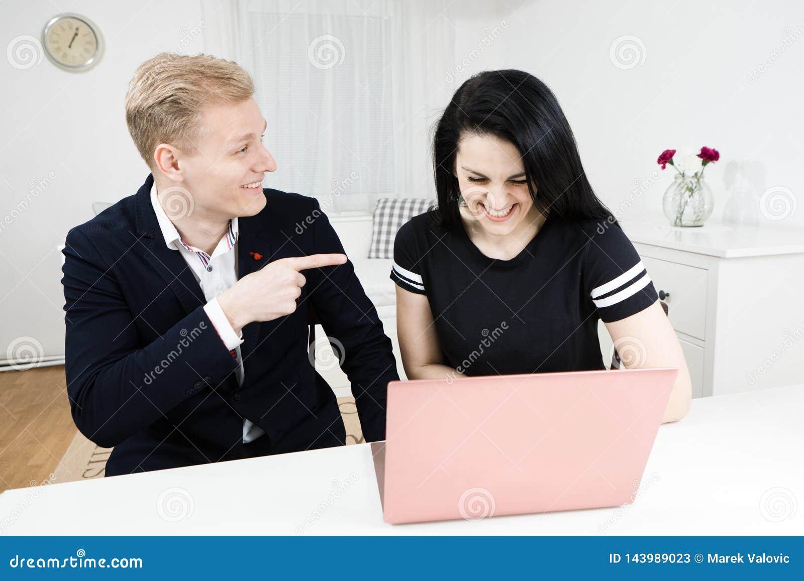 Trabalhos dos superiores com subordinado Dedo louro dos pontos do homem na mulher de cabelo preta