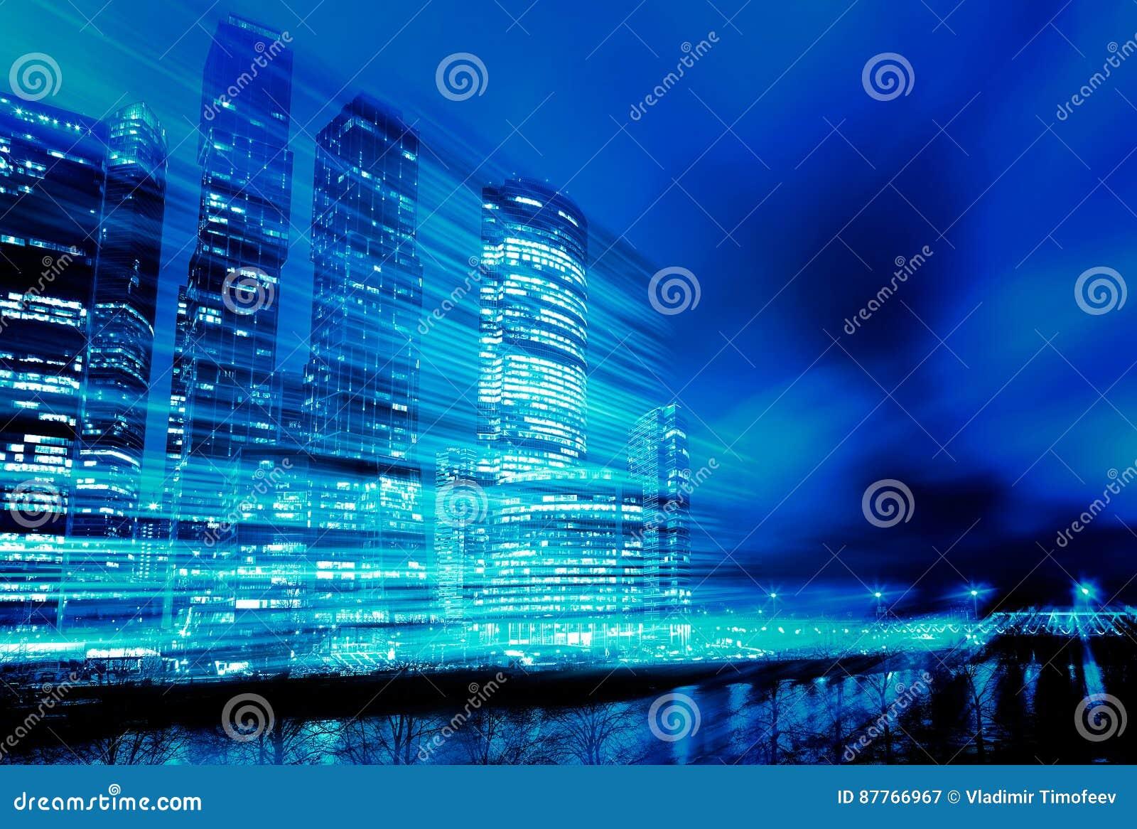 Tracce della luce sul fondo moderno della costruzione Concetto dei grattacieli nel mosso di notte Tonalità blu