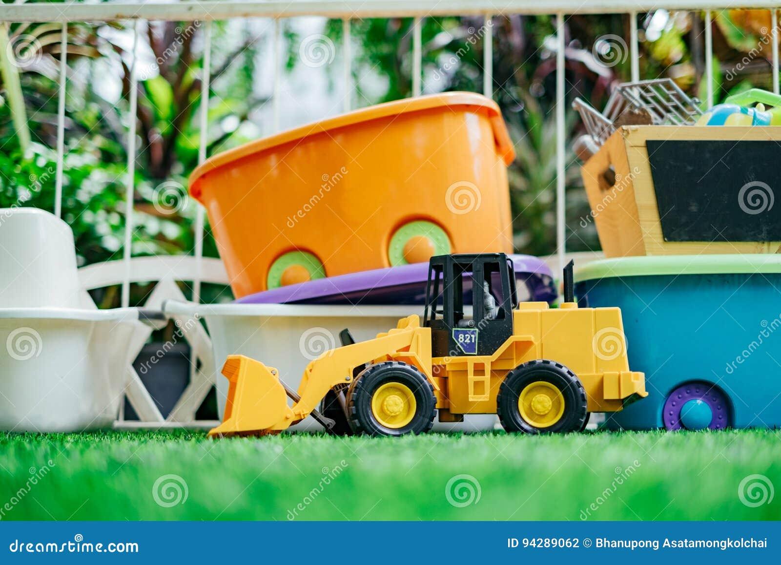 Tracktor-Spielzeugauto mit Spielzeugkisten im Garten