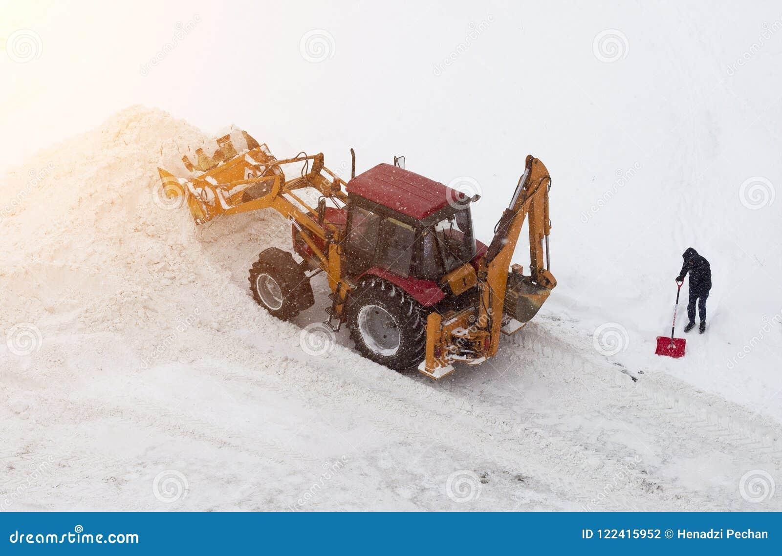 Tracteur et homme rouges avec une pelle sur le nettoyage de neige