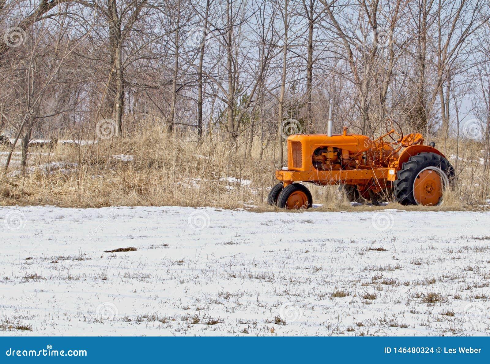 Tractor anaranjado en la nieve