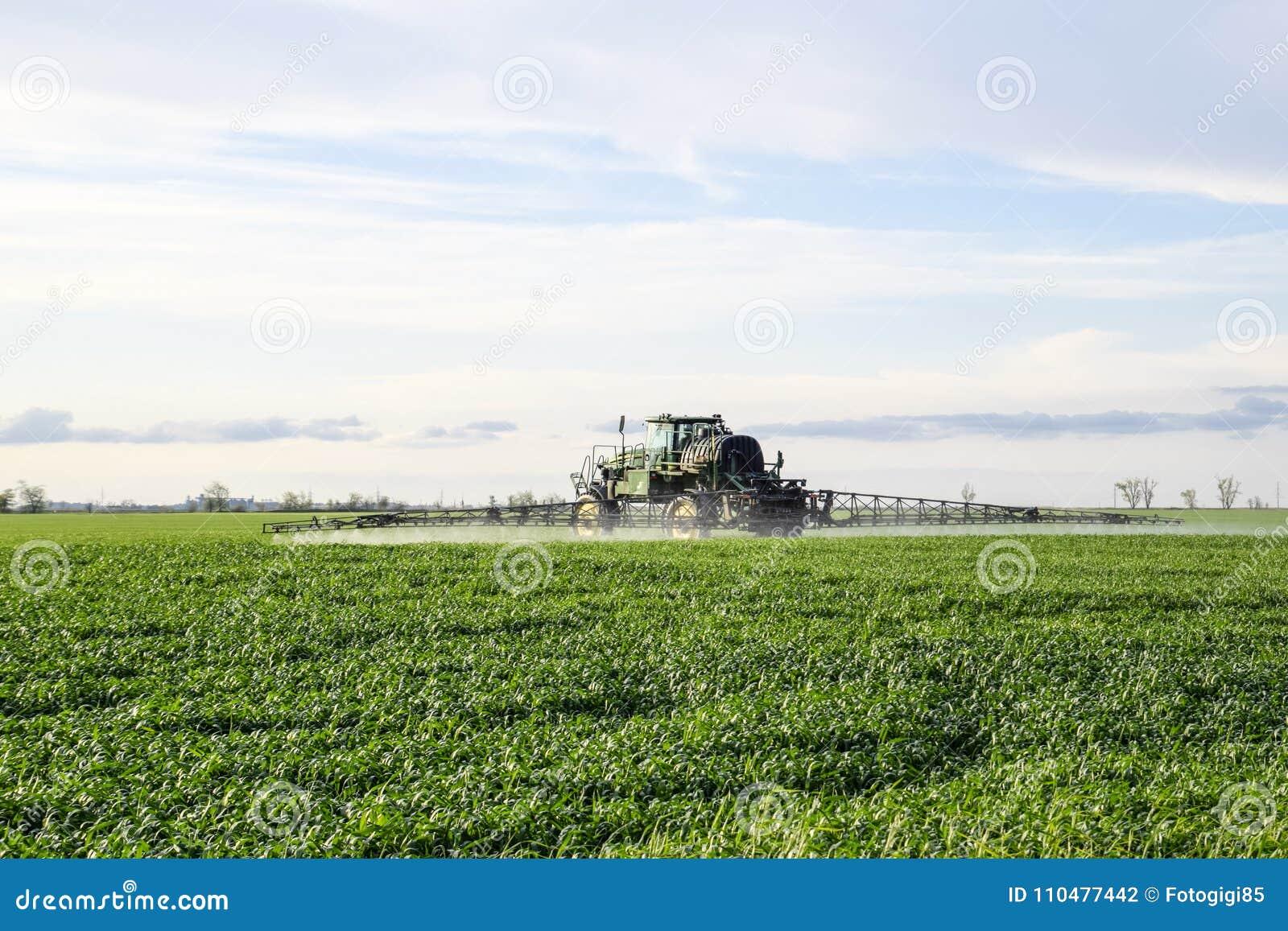 Tractor con un dispositivo del espray para el fertilizante finalmente disperso Tractor en el fondo de la puesta del sol El tracto