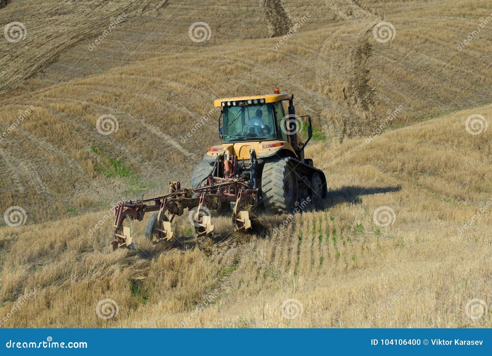 Tractor de correa eslabonada con la paleta en un campo biselado