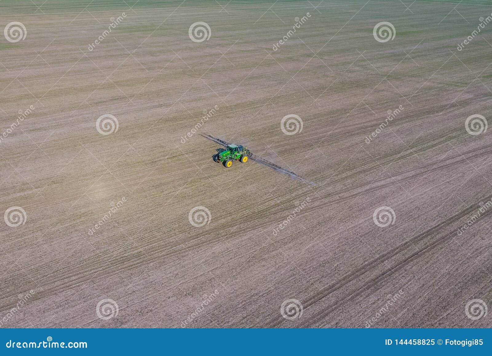 Tractor met scharnierend systeem om pesticiden te bespuiten Bevruchtend met een tractor, in de vorm van een aërosol, op het gebie
