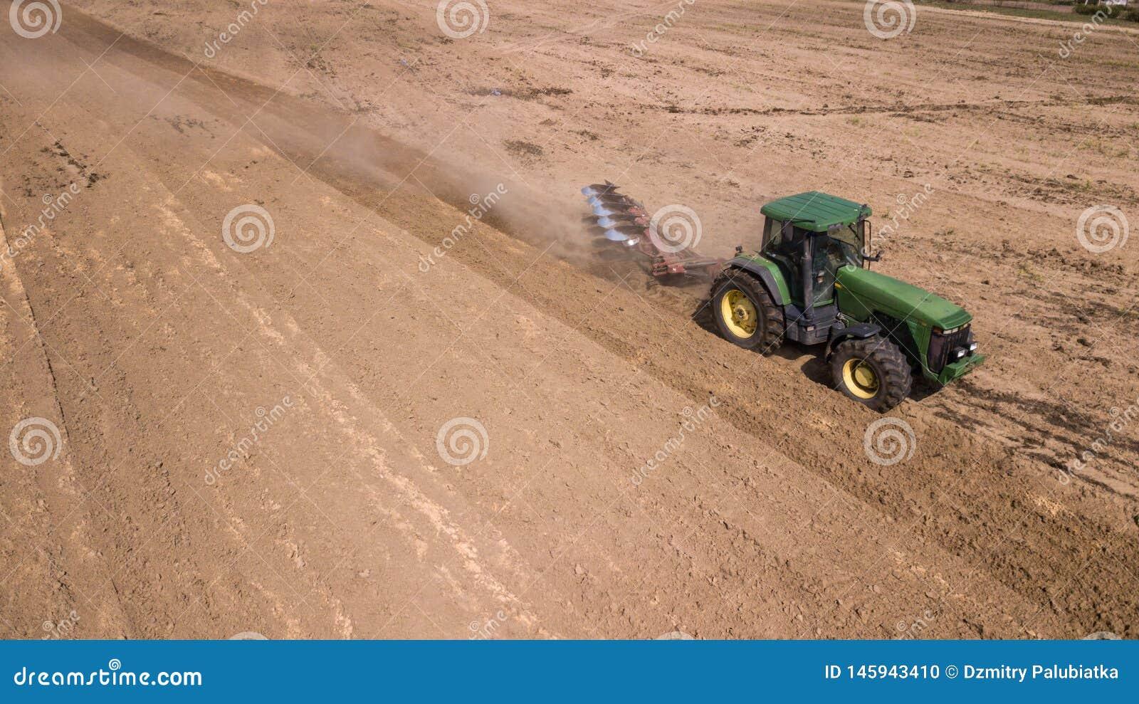 Tractor que ara la opini?n superior del campo, fotograf?a a?rea con el abej?n