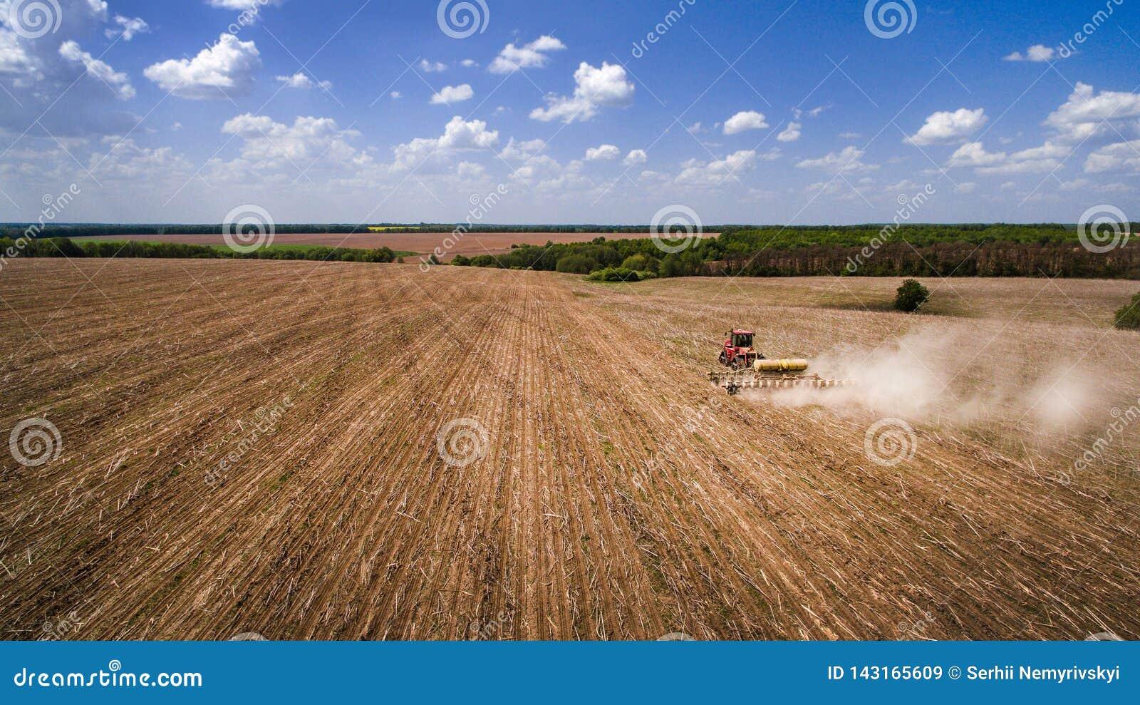 Tractor que prepara la tierra para sembrar dieciséis filas aéreas, el concepto de cultivo, siembra, arando el campo, el tractor y
