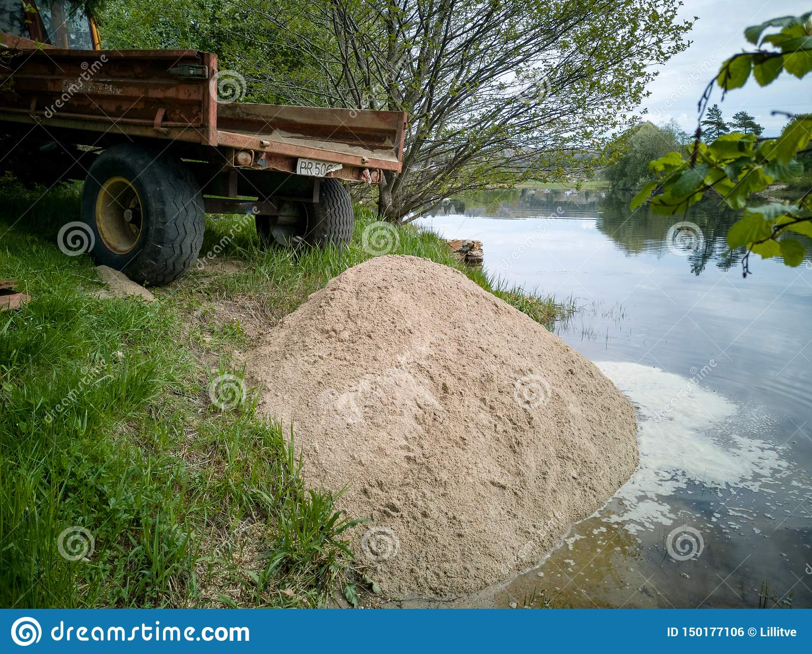 Tractor remolque que inclina una carga de la arena para crear la playa