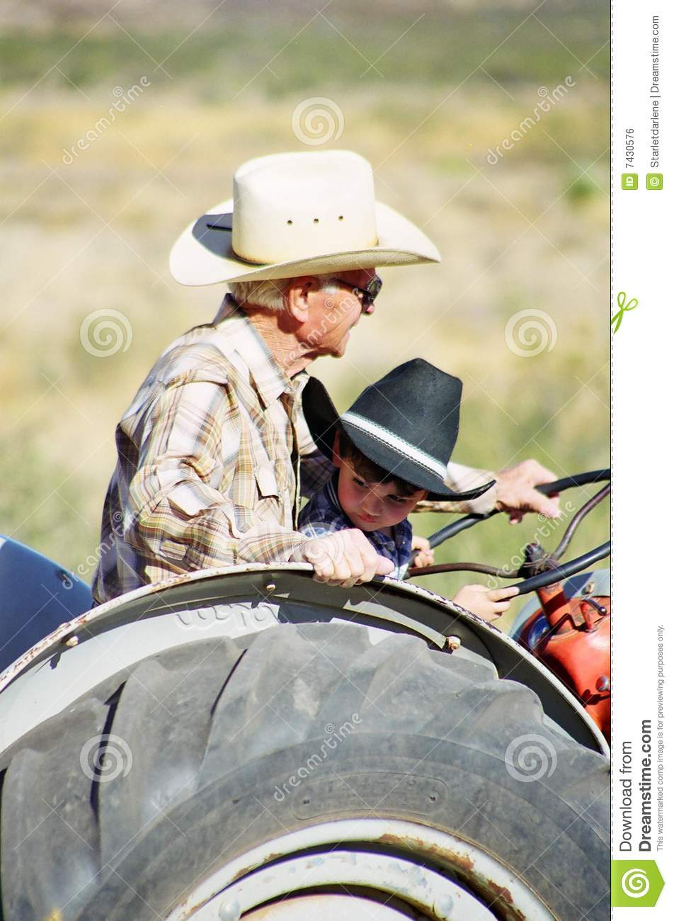 Boy On Tractor : Tractor ride for a little boy and grandfather royalty free