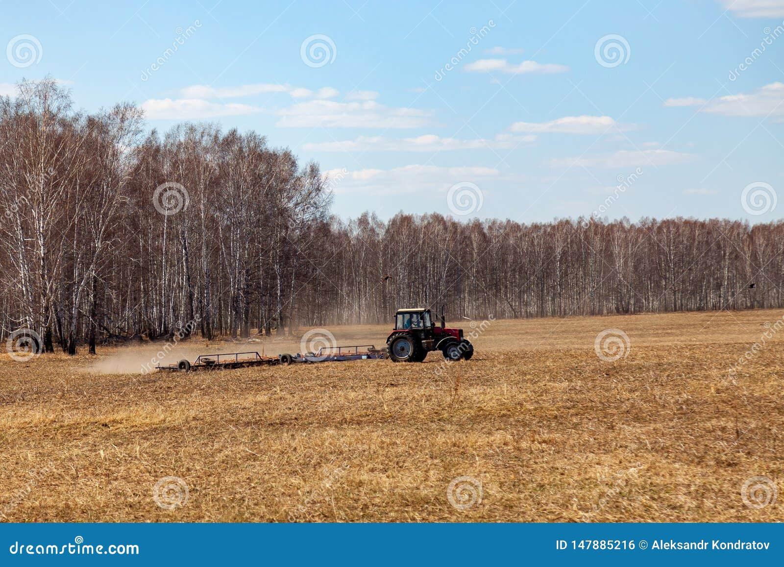 Tractor rojo con una paleta arrastrada para segar y escardar los campos para la agroindustria del color amarillo debajo del cielo
