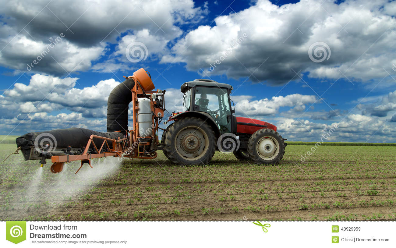 Tractor spraying soybean crops field