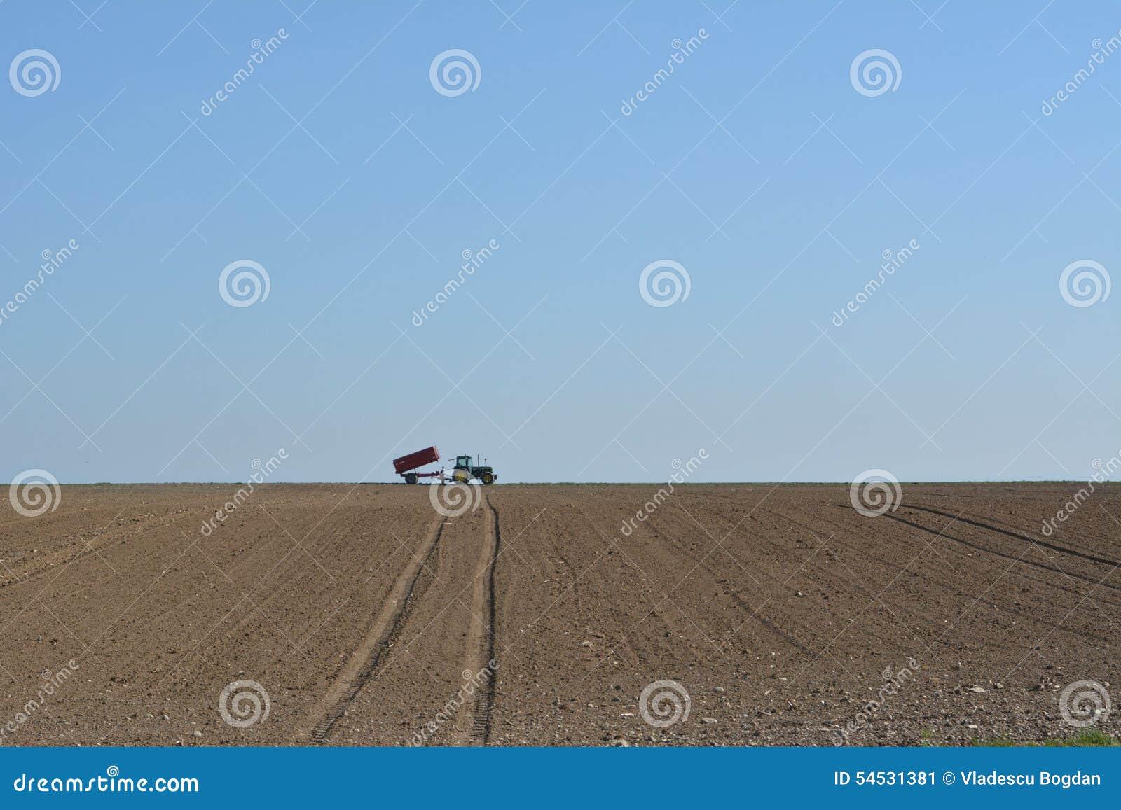 Tractor working on plowed field