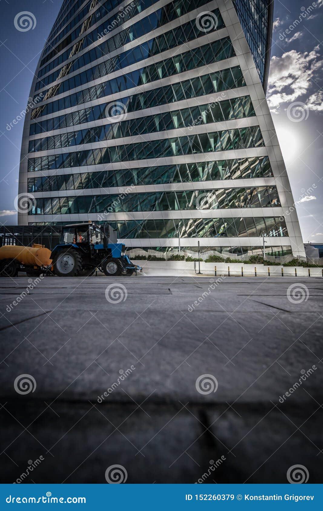Tractorritten op de weg tegen een wolkenkrabber