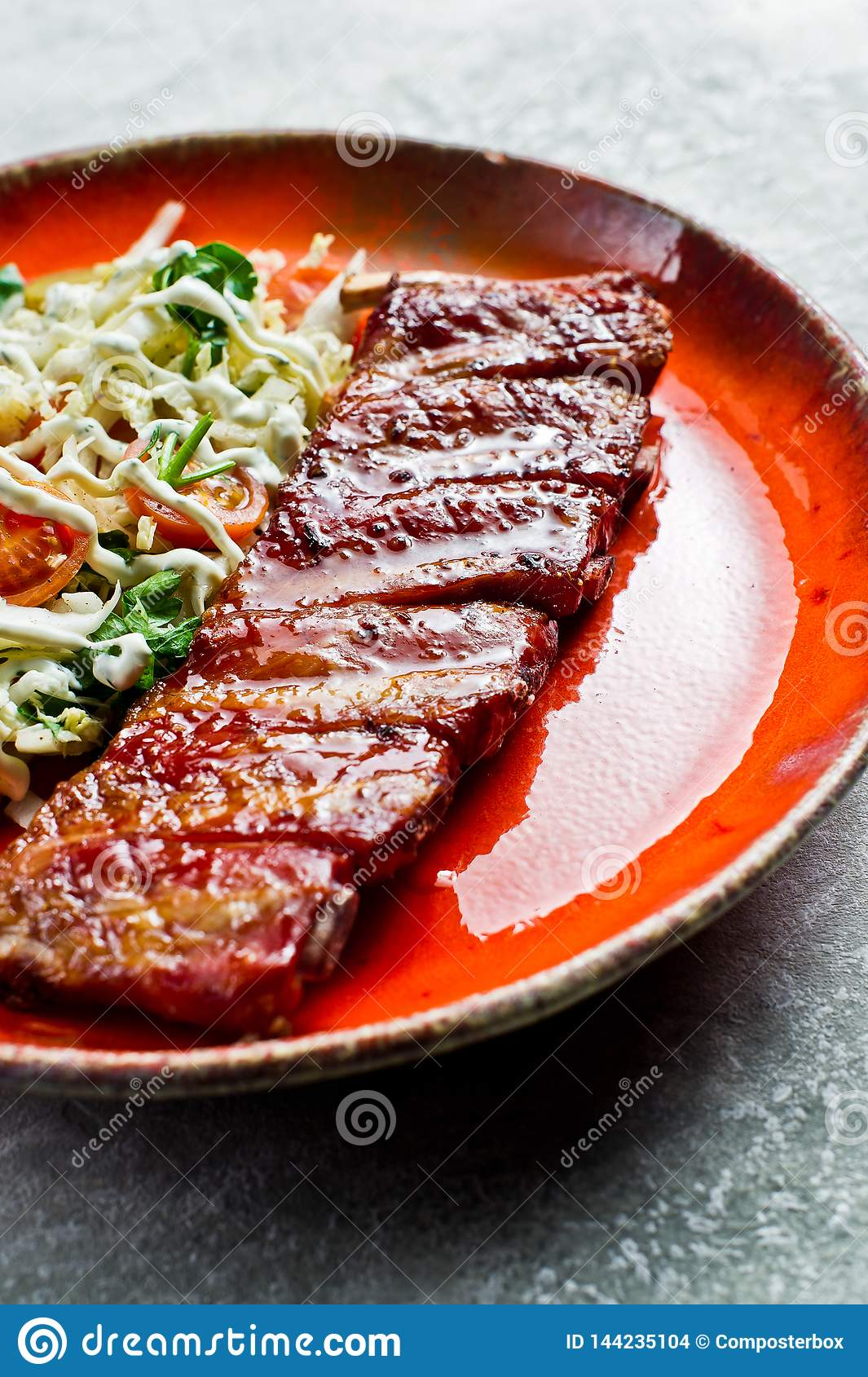 Traditional American barbecue pork ribs with a side dish of green salad. Grey backgroun