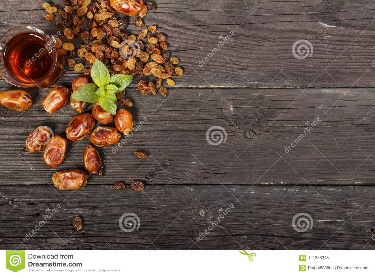 Traditional Arabic, Turkish Ramadan tea with dry dates and raisins on a wooden black table. Ramadan. Turkish fresh tea with dates.