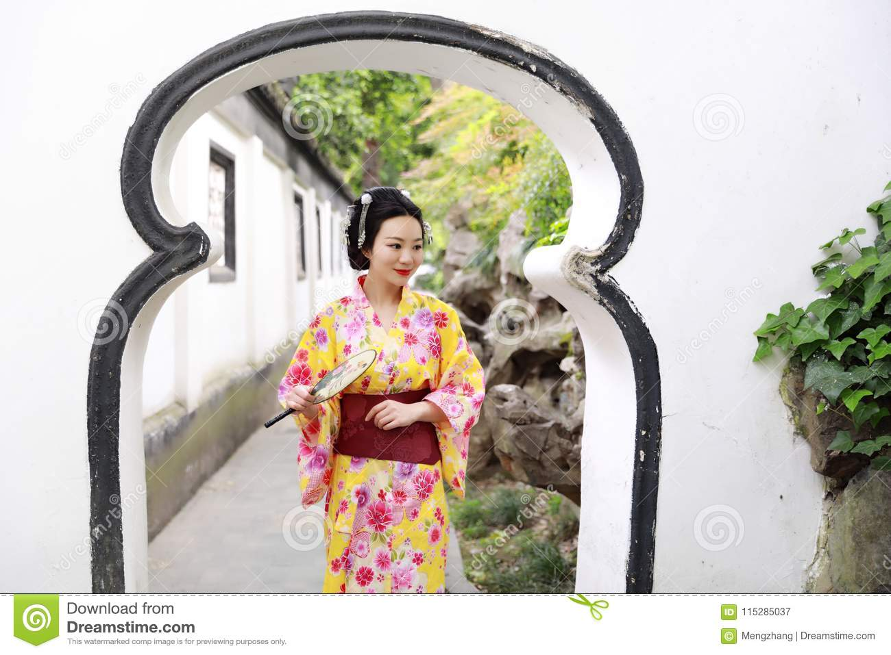 Traditional Asian Japanese beautiful woman wears kimono in a spring garden park stand by bamboo enjoy free time fan