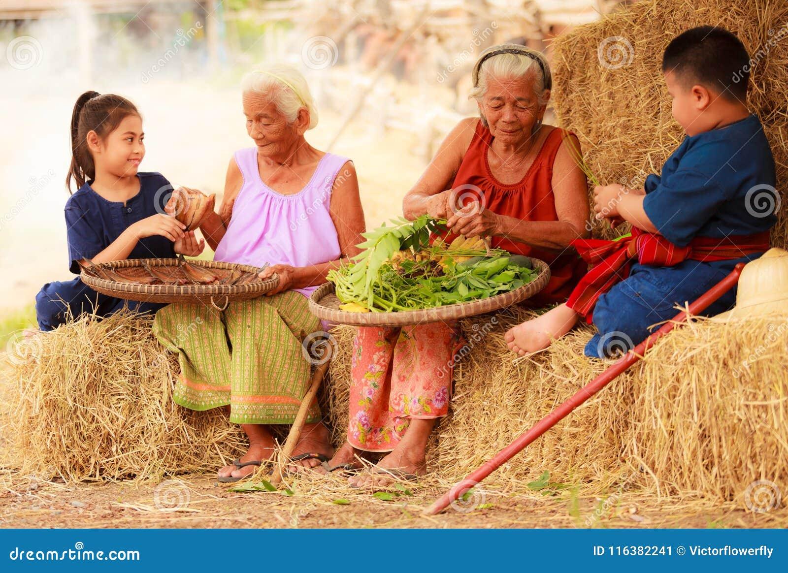 Traditional Asian Thai rural daily life, grandchildren in cultural costumes help their seniors preparing local food ingredients