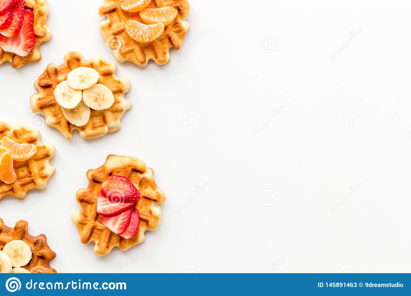 Traditional belgian waffles with fruit topings on white background top view mock up. Hot homemade breakfast. Traditional belgian waffles with fruit topings on stock photos